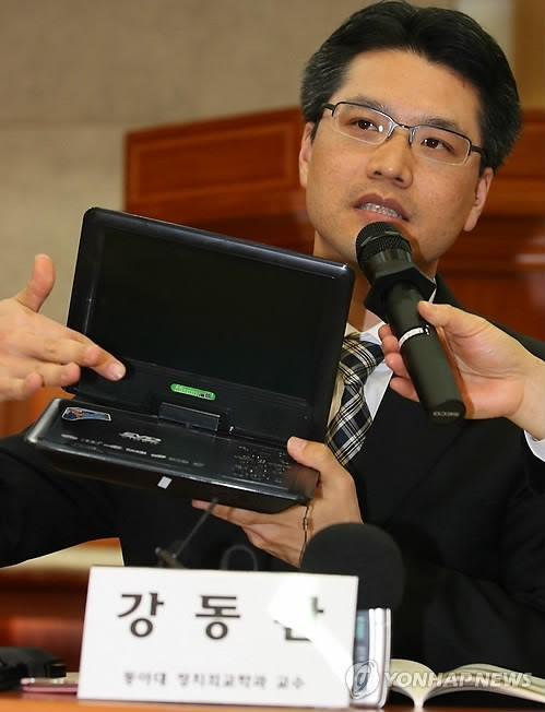 """Professor Kang Dong-wan of South Korea's Donga University shows a Chinese EVD portable video-playing device, referred to as """"Note TV or Note-tel"""" by North Koreans, in this photo dated Nov. 22, 2013. (Yonhap)"""