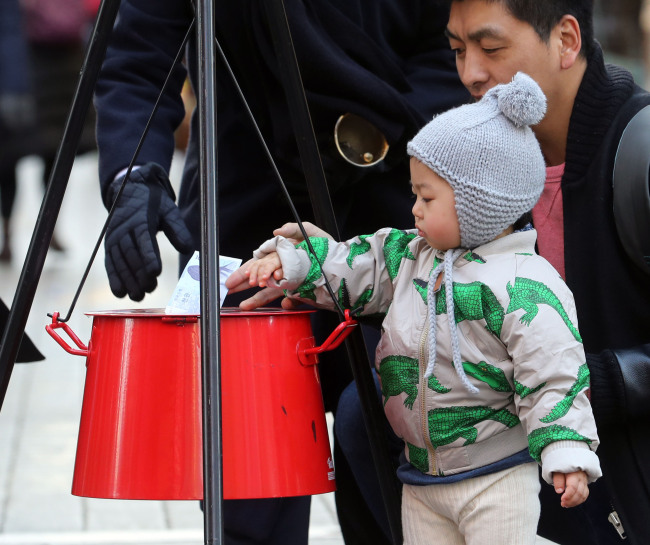 A child, with the help of his mother, drops money into the Salvation Army's red donation kettle in Myeong-dong, Seoul, on Dec. 1. (Yonhap)