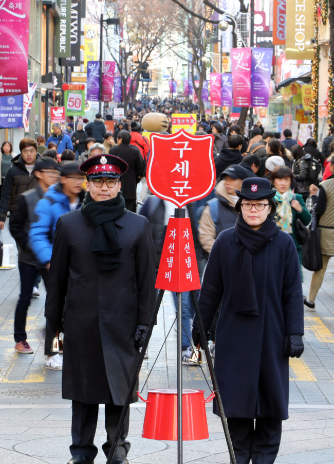 Salvation Army officials stand next to their signature red kettle on a street in Myeong-dong, Seoul, on Dec. 1. (Yonhap)