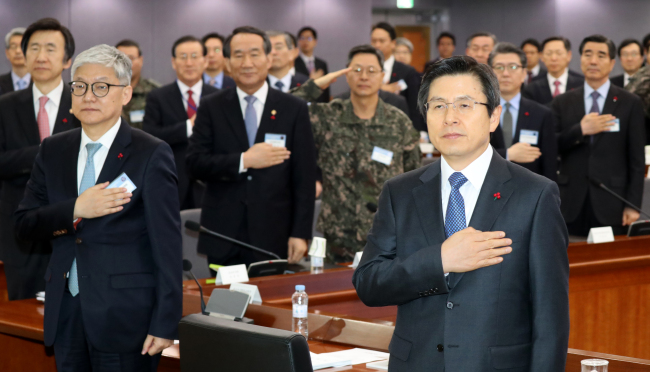 South Korea's Acting President and Prime Minister Hwang Kyo-ahn (right front) salutes the South Korean national flag during the New Year's policy briefing session on defense and diplomatic affairs at the government complex in Seoul on Wednesday (Yonhap)