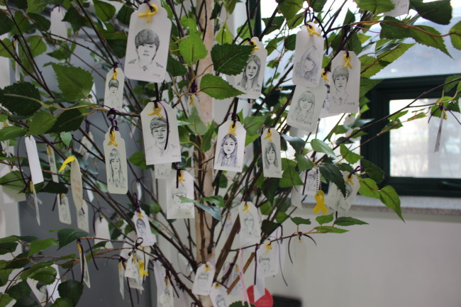 Portraits of the victims hang on a tree inside the relocated Memorial Classroom. (Jo He-rim/The Korea Herald)