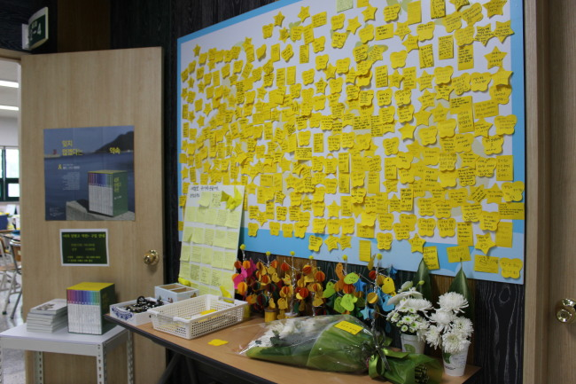 Yellow post-its containing messages from visitors stick on a board inside the relocated Memorial Class. (Jo He-rim/The Korea Herald)