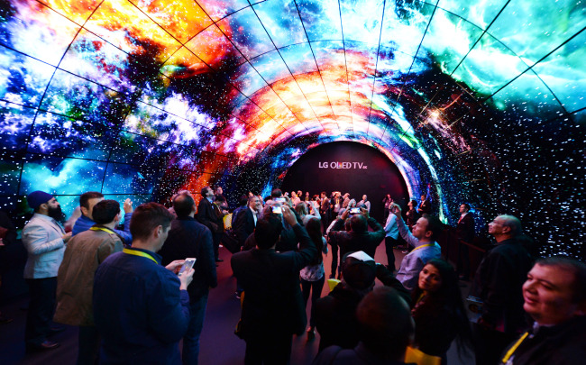 Visitors walk through the OLED tunnel established by LG Electronics at the Consumer Elelctronics Show 2017 in Las Vegas on Saturday. (LG Electronics)