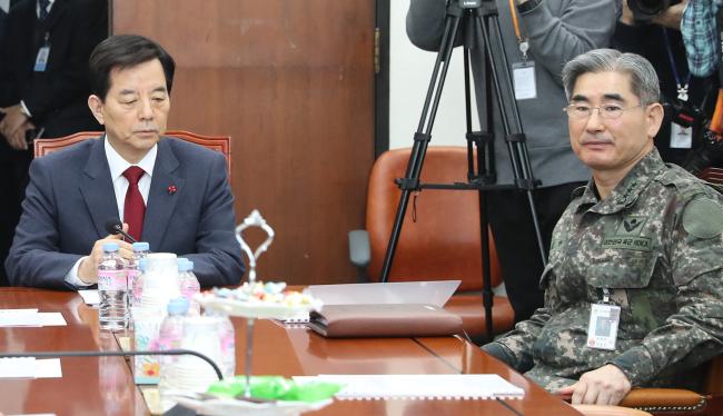 Defense Minister Han Min-koo (left) receives a briefing on the KADIZ breaches (Yonhap)