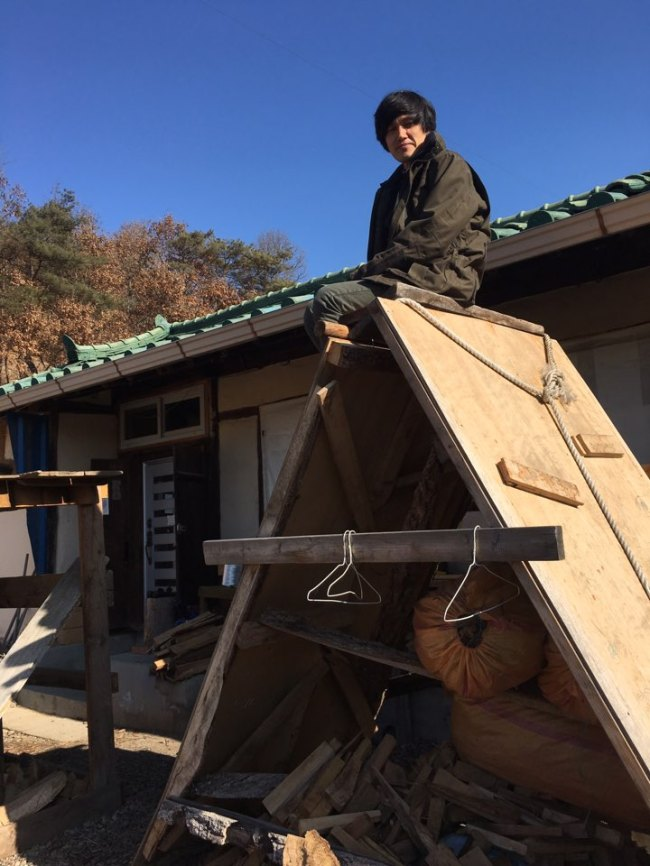 Pyun Hae-moon sits on a giant slide created with wooden boards by his children in front of his house in Andong. (Kim Da-sol/The Korea Herald)