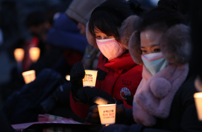 Despite cold weather, protesters participate in the anti-Park Geun-hye rally in Gwanghwamun, central Seoul, on Saturday evening. (Yonhap)