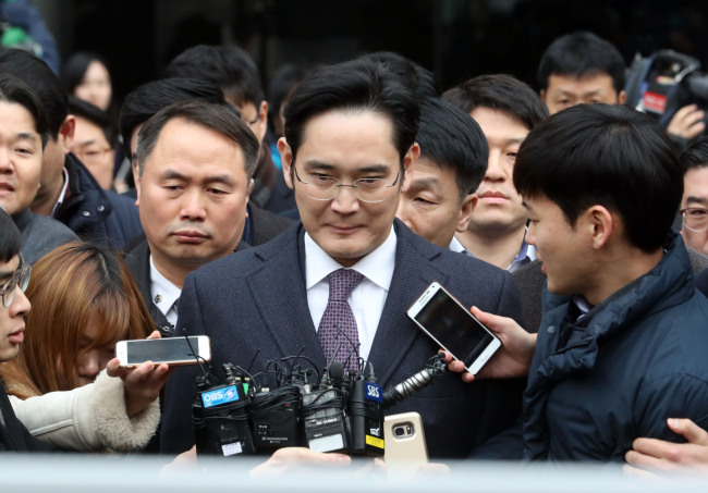 Samsung Electronics Vice Chairman Lee Jae-yong is surrounded by reporters as he leaves a local court in Seoul on Wednesday. (Chung Hee-cho/The Korea Herald)