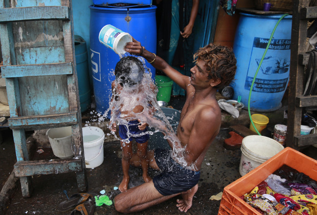 A man bathes his son on a hot afternoon in a slum in Mumbai, on May 23, 2016. (AP-Yonhap)