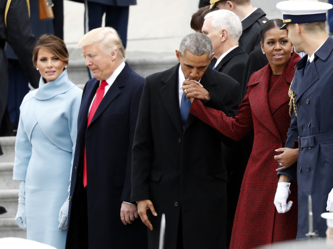 First lady Melania Trump stands with President Donald Trump as former President Barack Obama kisses the hand of his wife Michelle Obama, during a departure ceremony on the East Front of the U.S. Capitol, Jan. 20, 2017 in Washington. (AP Photo/Alex Brandon)