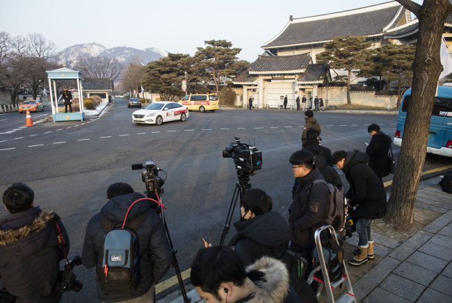 Photographers from the press wait for the special counsel investigators' arrival at Cheong Wa Dae on Friday. (Yonhap)