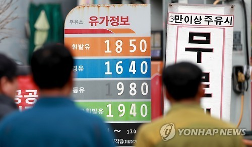 Customers look at oil prices listed at a gas station in Seoul on Jan. 8, 2017. (Yonhap)