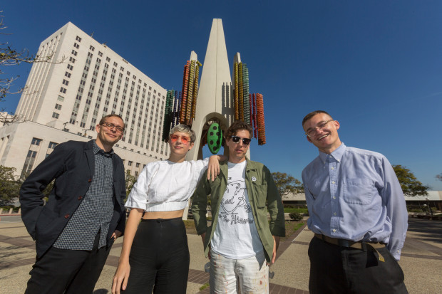 "From left: Tanner Blackman, Claire Evans, Jona Bechtolt and Tom Carroll, members of the Triforium project, pose with Joseph L. Young's Triforium, a ""polyphonoptic"" public sculpture, at the Fletcher Bowron Square in downtown Los Angeles on Feb. 1. (AP-Yonhap)"