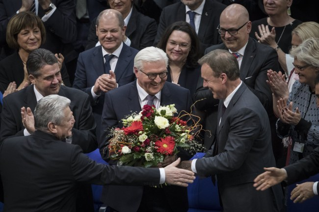Newly elected German President Frank-Walter Steinmeier (center) receives flowers and standing ovations during the Federal Assembly at the German 'Bundestag' parliament in Berlin on Sunday. (EPA-Yonhap)