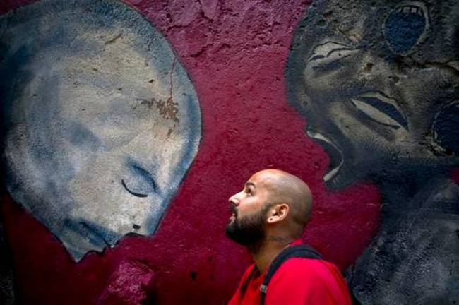 In this Feb. 9 photo, graffiti artist Yulier Rodriguez Perez poses with one of his works, painted on a wall in Old Havana, Cuba. (AP-Yonhap)