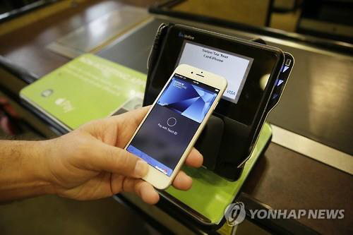 A user demonstrates the use of Apple Pay. (Yonhap)