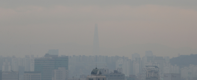 Fine dust covers the cityscape of Jongno-gu and Lotte World Tower in Jamsil, Seoul, on Thursday. (Yonhap)