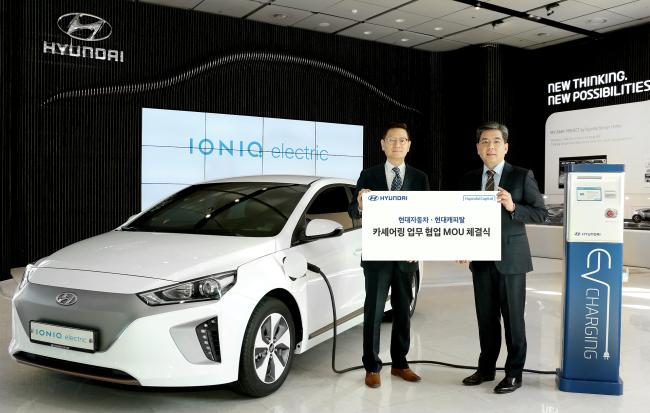 Chang Jae-hoon (right), a senior vice president of the customer value division at Hyundai Motor, and Lee Byung-hui, a vice president of the auto business division at Hyundai Capital, pose at the signing of the memorandum for electric car-sharing services. (Hyundai Motor Group)