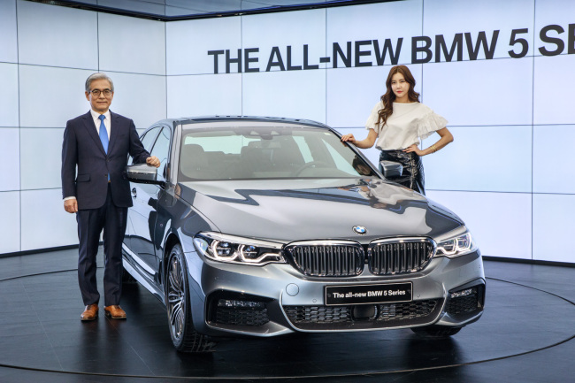 BMW Korea President Kim Hyo-joon (left) poses with the new BMW 5 Series during a launch event at the Parnas Tower in Seoul on Tuesday. (BMW Korea)