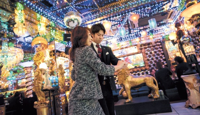 A woman dances with a male host at a host club in the Kabukicho red-light district in Tokyo. (AFP-Yonhap)