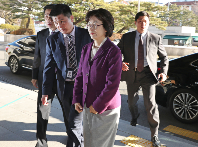 The Constitutional Court's acting Chief Justice Lee Jung-mi enters the court building Friday under the protection of police officers. The court requested earlier this week for close personal security of all its current justices, in response to escalating anti-impeachment protests. (Yonhap)