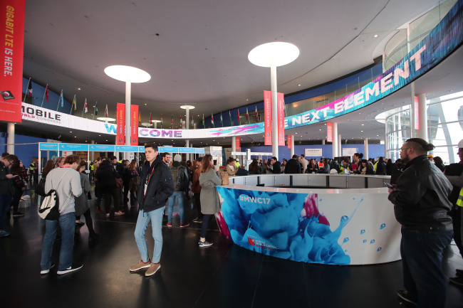 IT and communications industry officials walk around to register for the Mobile World Congress 2017 at the Fira Gran Via Exhibition Center in Barcelona, Spain, on Sunday. (Yonhap)