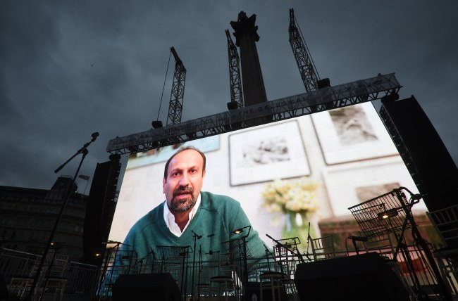 Iranian film director, Asghar Farhadi, is seen on a screen as he sends a video message during a screening of his Oscar-nominated film 'the Salesman' in Traflagar Square in London, Britain (EPA-Yonhap)