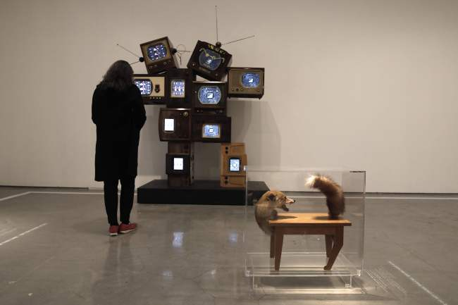 """A woman looks at the """"Allan and Allen"""" installation by Nam June Paik as she stands next to the """"Wolf Table"""" installation by artist Victor Brauner at the living room section of the """"No Place Like Home"""" exhibition in the Israel Museum in Jerusalem on Sunday. (AFP-Yonhap)"""