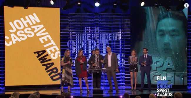 Director Andrew Ahn (center) accepts the John Cassavetes Award at the 2017 Film Independent Spirit Awards on Saturday. (Screen capture from YouTube)