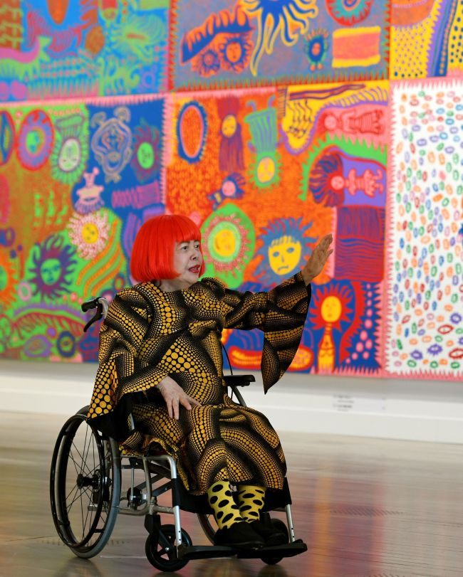 Japanese artist Yayoi Kusama waves at a photo session during a press preview of her exhibition titled