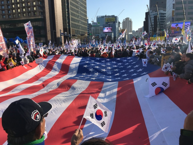 Conservative civic group members and President Park Geun-hye's supporters hold a giant US flag during their anti-impeachment protest held in central Seoul on Saturday. (Ock Hyun-ju/The Korea Herald)