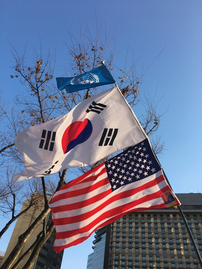 From top hangs flags of the United Nations, South Korea and the United States of America at an anti-impeachment protest in central Seoul on Saturday. (Ock Hyun-ju/The Korea Herald)