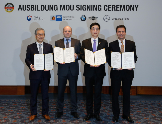 From left, BMW Group Korea CEO Kim Hyo-joon, Korean-German Chamber of Commerce and Industry Chairman Stefan Halusa, Education Minister and Deputy Prime Minister for Social Affairs Lee Joon-sik and Mercedes-Benz Korea CEO Dimitris Psillakis pose at the signing of a memorandum for understanding for the new Ausbildung vocational program at the Millennium Seoul Hilton on Monday. (Yonhap)