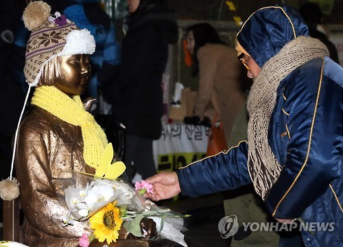 ASouth Korean citizen offers a flower to the statue of a girl, symbolizing the hundreds of thousands of Korean women who were mobilized as sex slaves for Japan's World War II soldiers, in front of the Japanese Embassy in Seoul on Jan. 9, 2016. (Yonhap)
