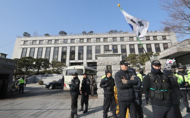 Police guard the Constitutional Court in Seoul on Thursday ahead of the final ruling Friday in President Park Geun-hye's impeachment trial