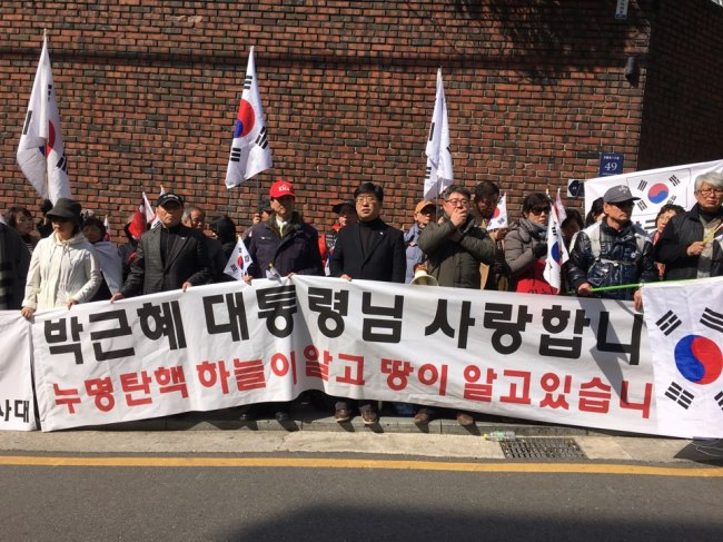 """Former President Park Geun-hye's suppporters hold a banner reading """"We love you President Park Geun-hye"""" during a rally in front of her private residence, in southern Seoul, Monday. Ock Hyun-ju/The Korea Herald)"""