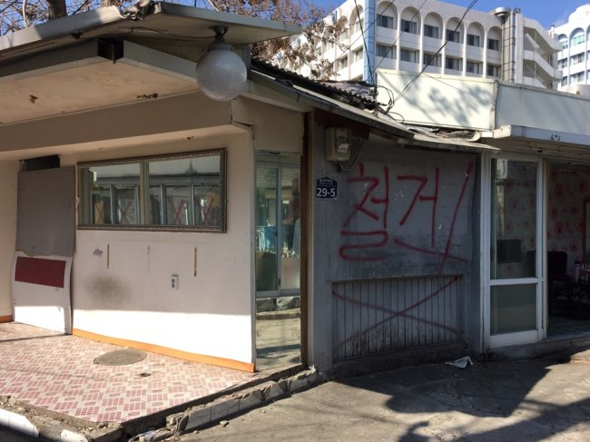 """The abandoned houses are left with shattered windows and large red letters spelling out """"demolition"""" written on broken walls. (Kim Da-sol/The Korea Herald)"""