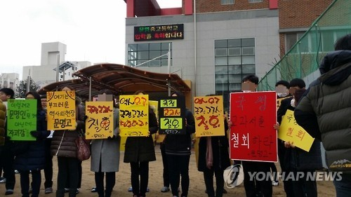 Students and parents hold up signs at Munmyeong High School in Gyeongsan on March 2, to demand that the school cancel its adoption of state-authored history textbook. (Yonhap)