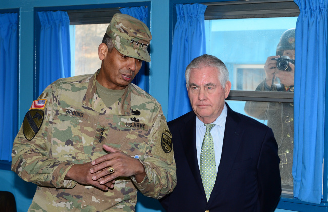 A North Korean soldier takes a snapshot from outside the window while US Secretary of State Rex Tillerson (right) listens to USFK Commander Gen. Vincent K. Brooks during his visit to Panmunjeom, the truce village on the inter-Korean border, Friday. (Yonhap)