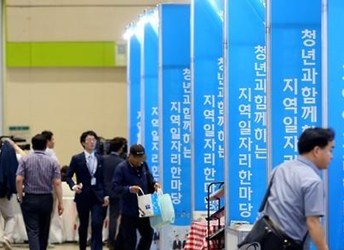 Young job seekers search through booths at a job fair for youth in Seoul (Yonhap)