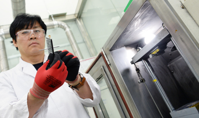 LG Electronics employee carries out a nail penetration test by penetrating a sharp nail into a battery. (LG Electronics)