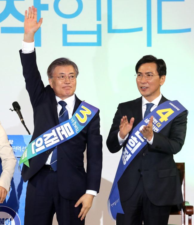 Presidential front-runner Moon Jae-in (left), beside his rival An Hee-jung, celebrates after winning the second primary race in Daejeon, Wednesday. (Yonhap)