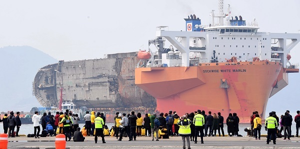 The Sewol ferry is brought to a port in Mokpo on Friday after it was lifted from where it sank some three years ago in the country's southwestern waters. (Yonhap)