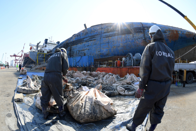 Workers clear mud from the Sewol (Yonhap)