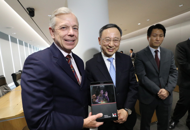 Verizon CEO Lowell McAdam (left) and KT CEO Hwang Chang-gyu demonstrate a hologram video call via a tablet PC at the KT headquarters in Gwanghwamun, central Seoul, on Monday. (KT)