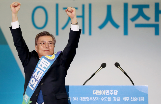 Moon Jae-in (left) raises his hands during the Democratic Party of Korea's primary race held Monday at Gocheok Sky Dome in western Seoul. (Yonhap)