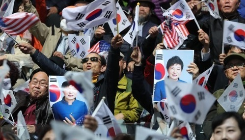 Supporters of former President Park Geun-hye wave national flags at an inaugural ceremony of a political party in Seoul on April 5, 2017. Park's loyalists formed the new Saenuri Party with two representatives of a civic group supporting the former president as the co-chiefs. (Yonhap)