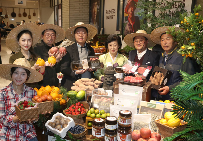 Holding their own local produce, farmers from different regions pose at the 2017 Shinsegae Farmers Market on Thursday. Shinsegae's farmers market project aims to directly connect local produce to consumers. The event was held at Shinsegae Department Store's main branch in Jung district, Seoul. (Yonhap)