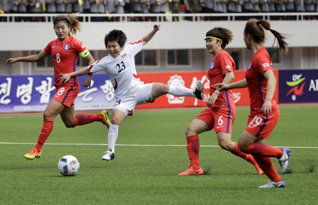 South Korea's Cho So-hyun (left) and North Korea's Sung Hyang-sim (center) run after the ball during their AFC Women's Asian Cup Jordan 2018 qualifying match at the Kim Il Sung Stadium on Friday in Pyongyang, North Korea. (AP)