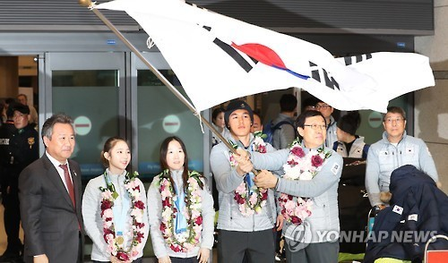 Kim Sang-hang (R), head of the South Korean delegation to the Sapporo Asian Winter Games, and Kim Magnus, cross-country skiing gold medalist, wave the national flag at Incheon International Airport after returning from the competition on Feb. 27, 2017. (Yonhap)