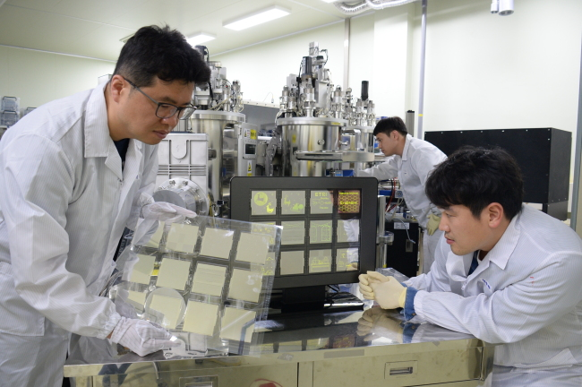 ETRI researchers work on graphene-based transparent electrodes for organic light-emitting diode panels at its research center in Daejeon. (ETRI)